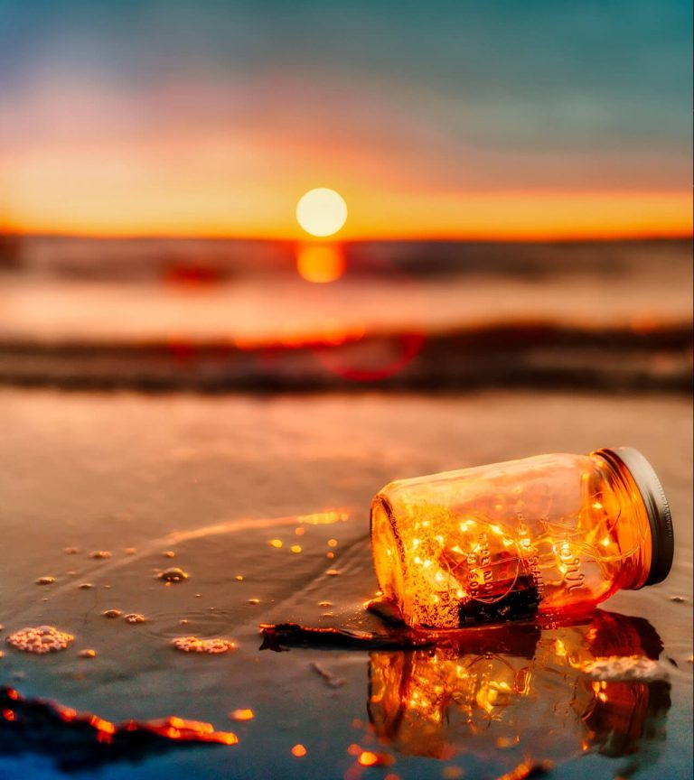 lights in jar lying on beach at sunset