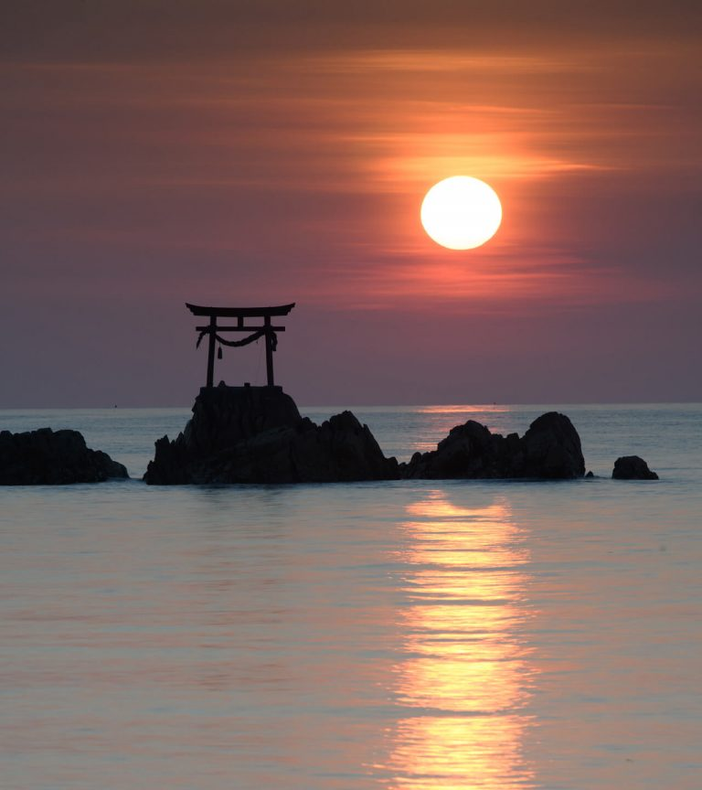 japanese scene with arch monument at sunset