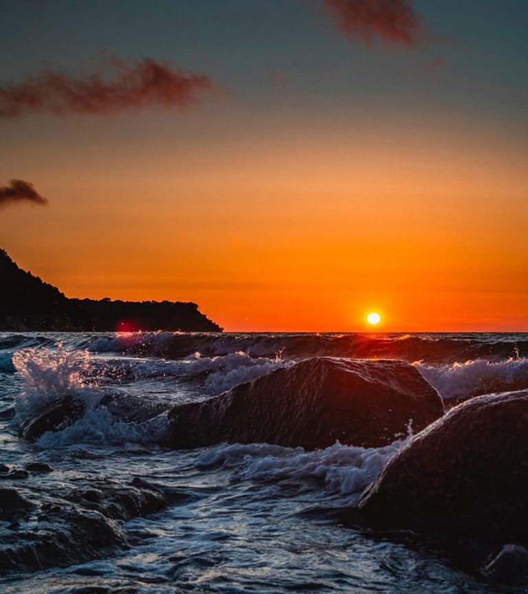 Sunset over ocean and rocks