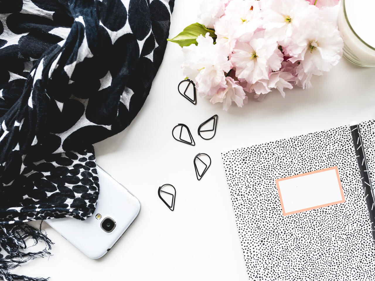 notebook, flower, paperclips and black and white print scarf