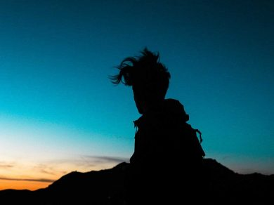 silhouette of young boy with wildly untidy hair sitting on rock with sunset behind